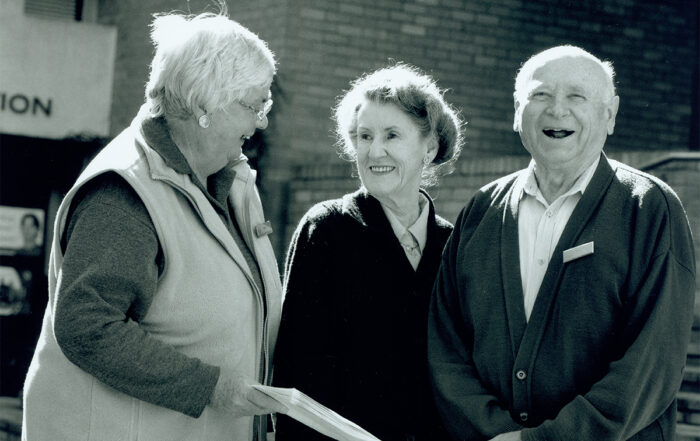 Two elderly women and an elderly man volunteering at Open Support