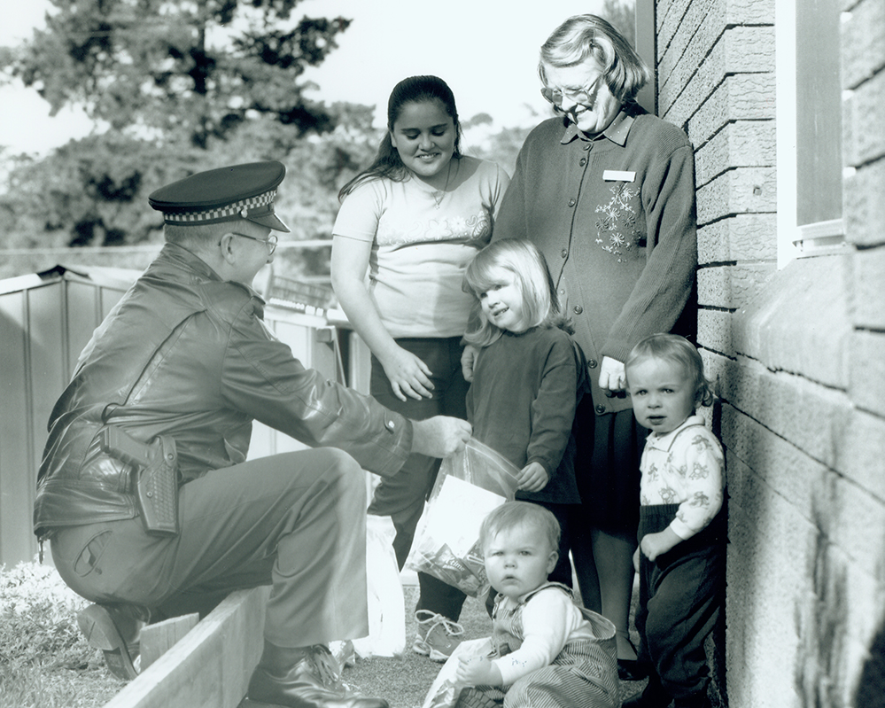 A Liverpool policeman, a woman and children in front of crisis shelter for domestic violence
