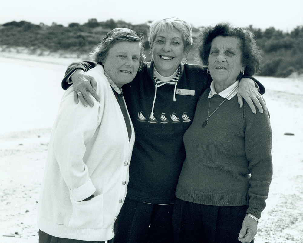 Three women smiling and sharing a nice moment as part of the Visit Program