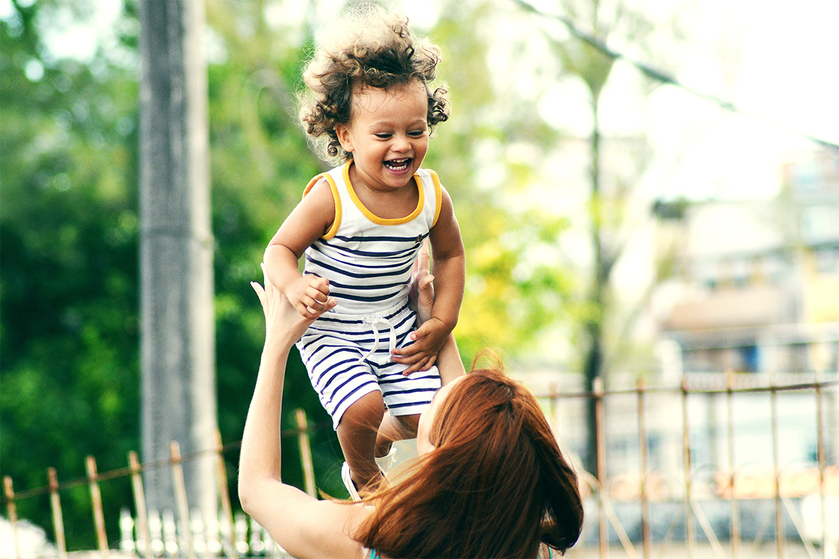 Laughing child with mother in safe environment with bright future
