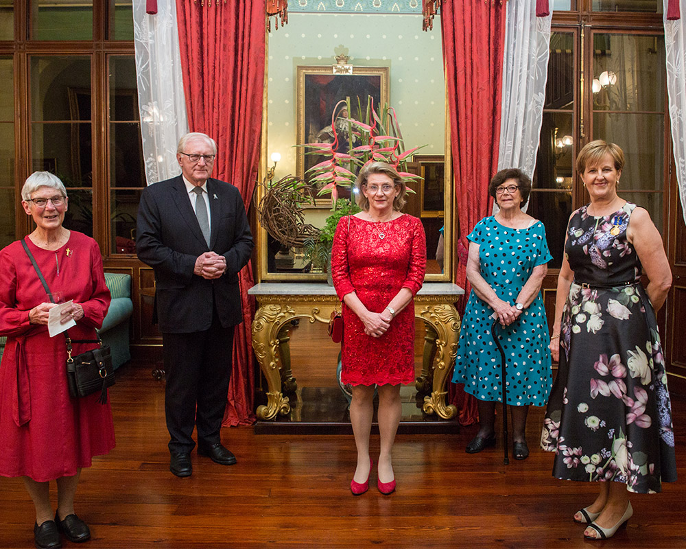 Five people standing in beautiful room celebrating anniversary