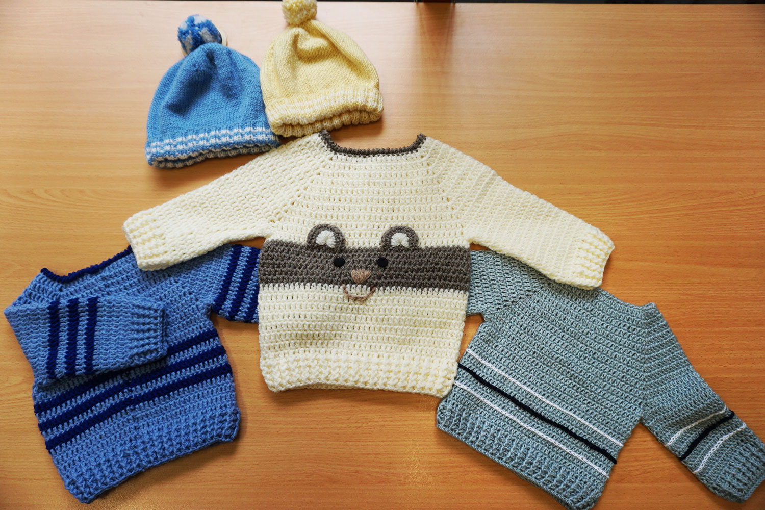 Child's crocheted jumpers and knitted beanie