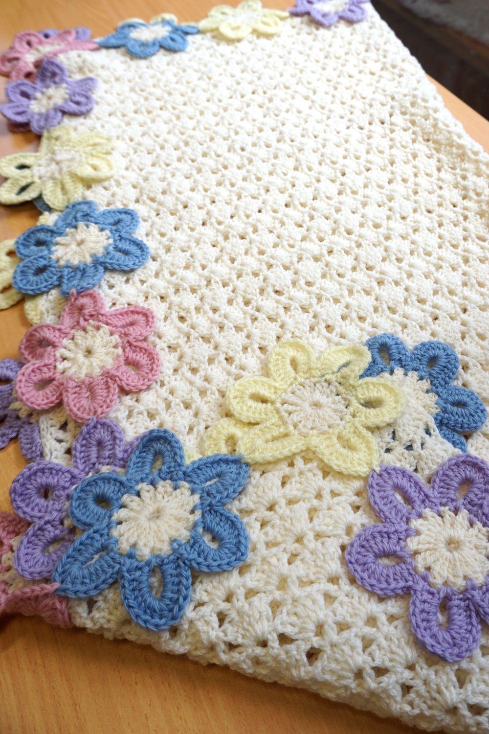 Beautifully crocheted cream patterned blanket and edged with colourful crocheted flowers