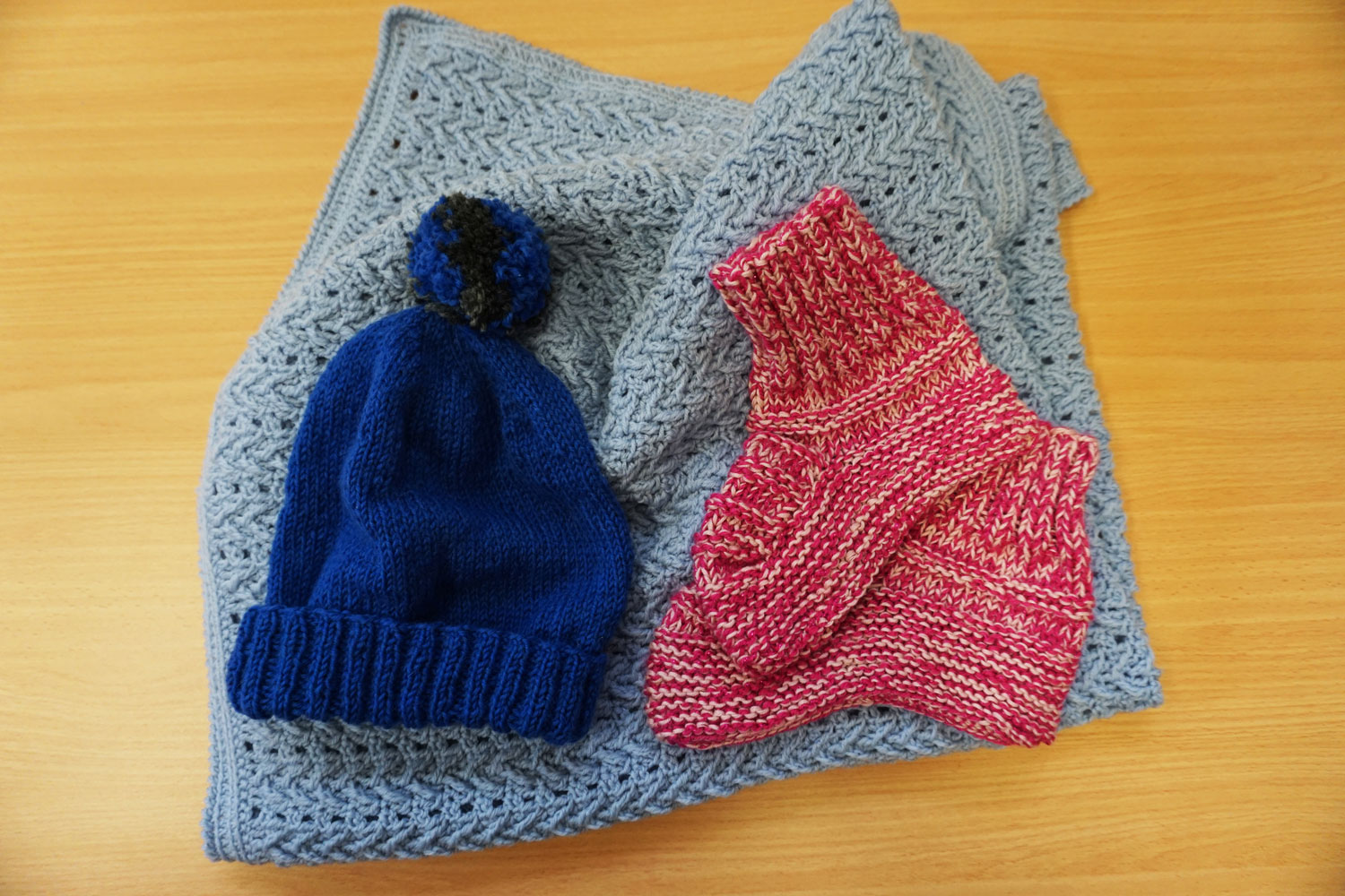 Knitted wool beanie with pom-pom ; pink bedsocks ; crocheted intricate pattern blanket – All 100% pure Australian