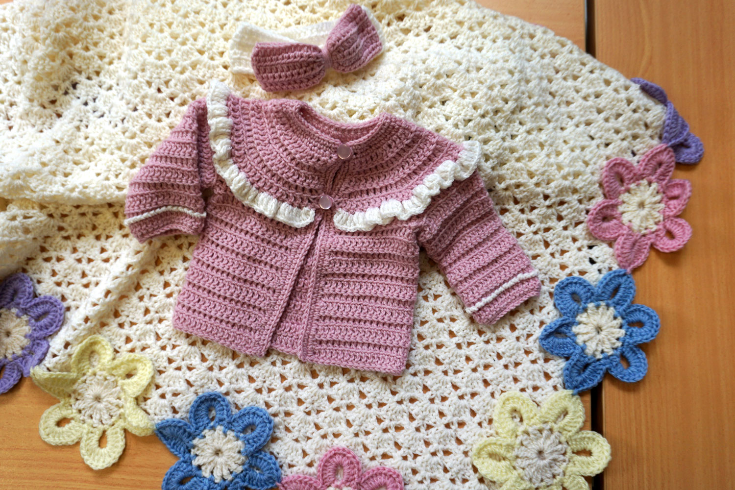 Dusty pink crocheted babies jacket with white trim and matching adorable headband